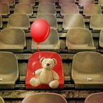 Rows of brown seats with one read seat in the middle. A teddy bear holding a red balloon sits on the red seat