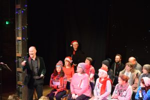 Audience, many wearing Christmas hats at a raffle during a fundraising event