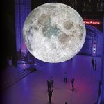A huge full moon shines over several people who look tiny in comparison. Pictured inside a large museum space.