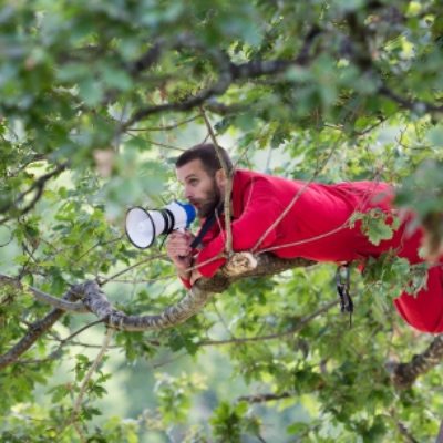 Bearded man with megaphone draped in a red blanket suspended in a leafy tree