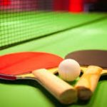 Two table tennis bats with a ball in-between lying on a green table with net in the background