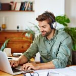Shot of a man sitting at home wearing headphones and working on a laptop