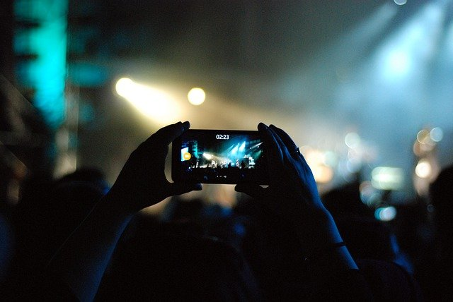 Someone filming a concert on their smartphone