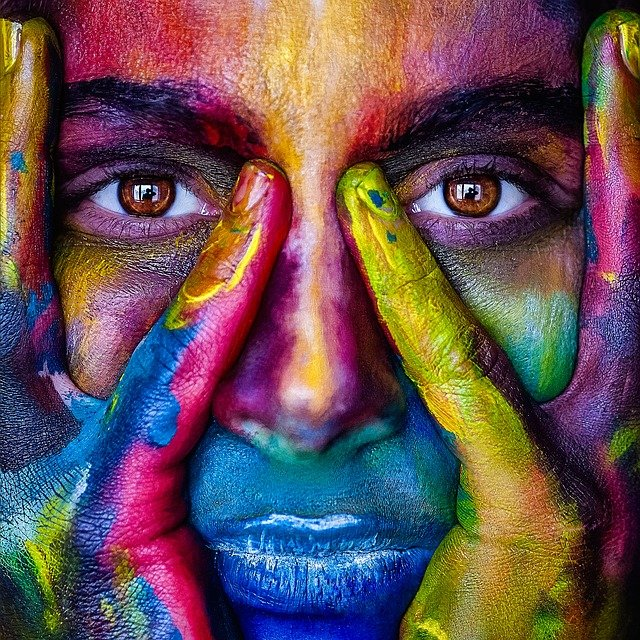 A face of a young, black woman stares directly at us. Her hands clasp her head with her little fingers placed on either side of her nose. Her face is brightly painted with many different colours of paint.