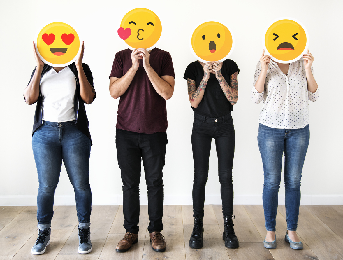 People holding emojis in front of their faces