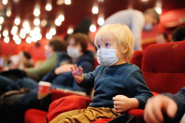Toddler wearing a face mask watching movie in the cinema.