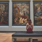 Woman sitting on a bench in a gallery looking at classical paintings