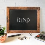 Small blackboard with the word fund with a calculator, plant, pen and dog clips.