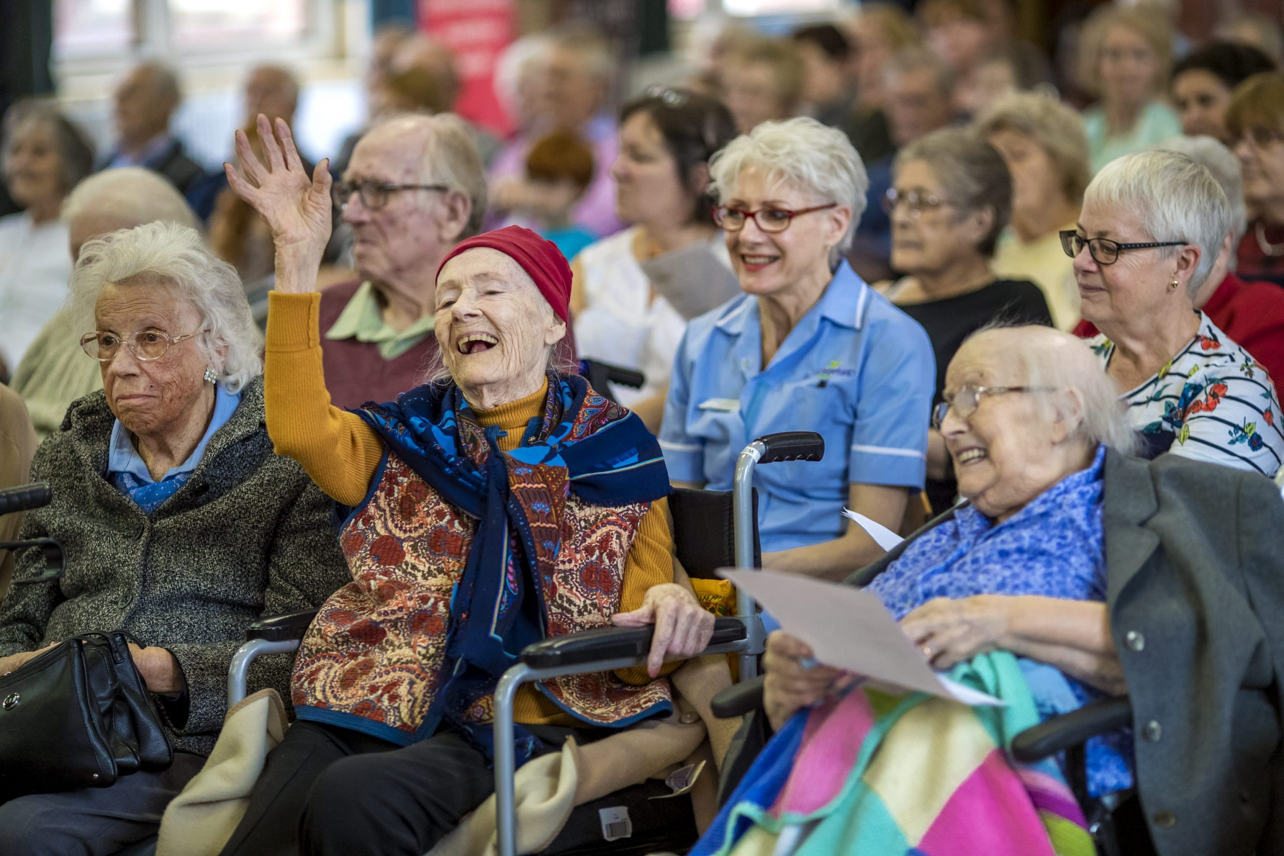 Older female audience member in wheelchair dancing to music