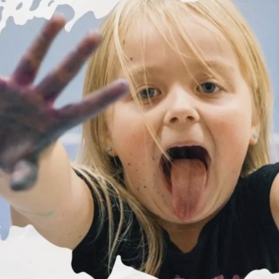 A young girl with tongue sticking out and outstretched hand covered in black paint.