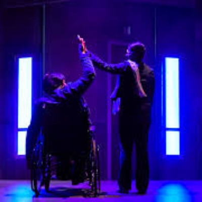 Two figures seen from the back, one in a wheelchair giving each other a high five.