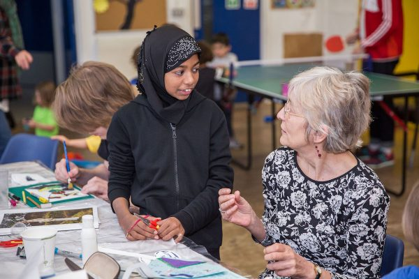 Child looks at older woman, both doing crafts