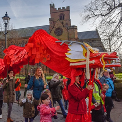 A long, red, paper dragon being carried through a village street by a group of excited adults and children