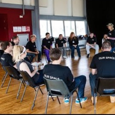 A large group of seated people in a theatre rehearsal space