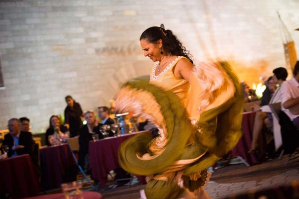 A flamenco dancer swirls a yellow dress in front of seated diners.