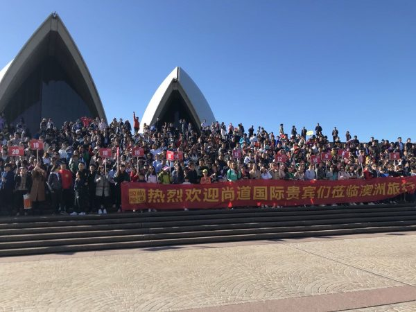 Hundreds of waving people on the steps to the Sydney Opera House in front of a long, thin, red banner with Chinese writing.