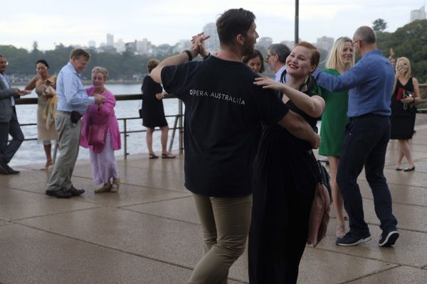 Five couples dance on an outside balcony with Sydney Harbour in the background.