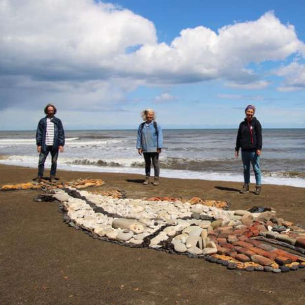 3 people on a beach behind a large, flat sculpture of a fish lying on the sand