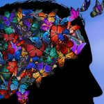 A silhouette of a face with the top half full of colourful butterflies esacping into a deep blue background