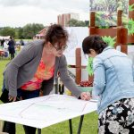 Two women in a park drawing on a map on a table