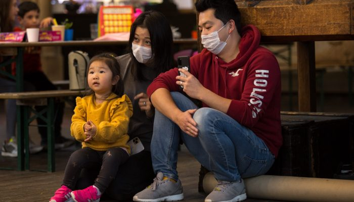 Family sitting together with masks watching an activity. Man filming it on his phone.