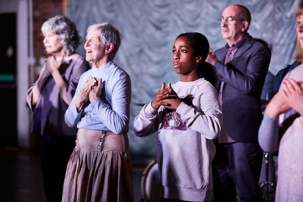 Older people and young girl facing camera with hands crossed over their chests