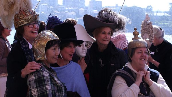 A group of audience members dressed in stage hats and masks