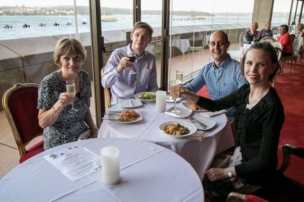 A family of four, mum, dad and a grown-up son and daughter raising glasses of wine. Each has a plate of delicious food in front of them.
