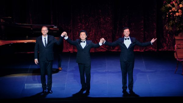 Three male opera singers in black suits join hands to take a bow on stage.
