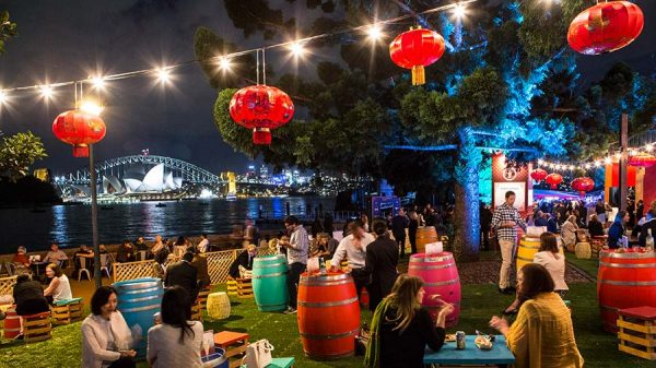 People talking, eating and drinking in The Qantas Garden Bar . Some are sitting on the grass, some on low stools. Colourful barrels are used as tables. Red Chinese lanterns provide a soft glowing light.
