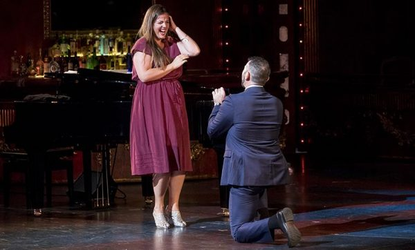 A man in a suit is on bended knee offering a ring in a box to a delighted, laughing woman