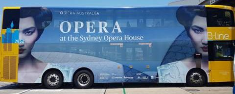 An advert promoting opera at the Sydney Opera House takes up most of the side of yellow bus