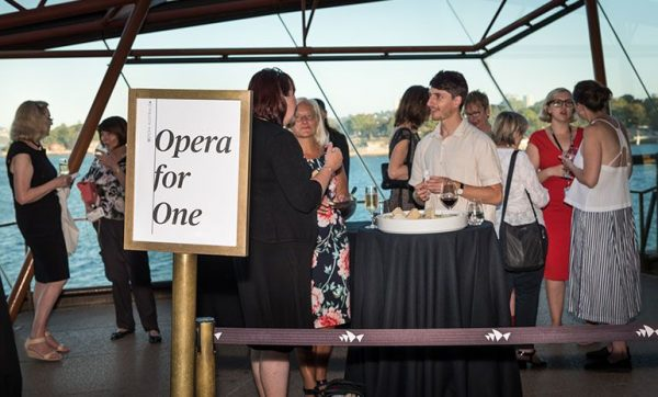 Several people socialising on the outdoor balcony near a large sign saying 'Opera for one'