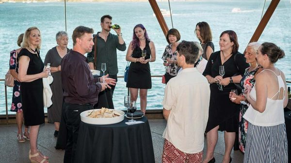 A large group of customers standing on a n outside balcony overlooking the water at Sydney Opera House