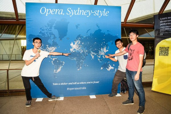 3 young men point at where they have come from on a lrage blue map of the world in the theatre foyer.