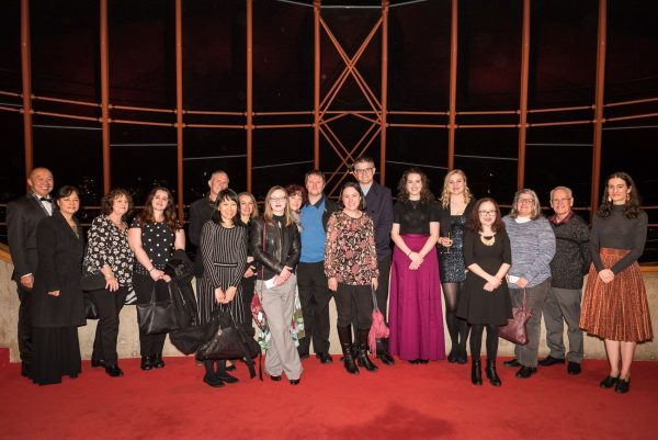 A diverse group of 18 people standing in a line in the theatre foyre.