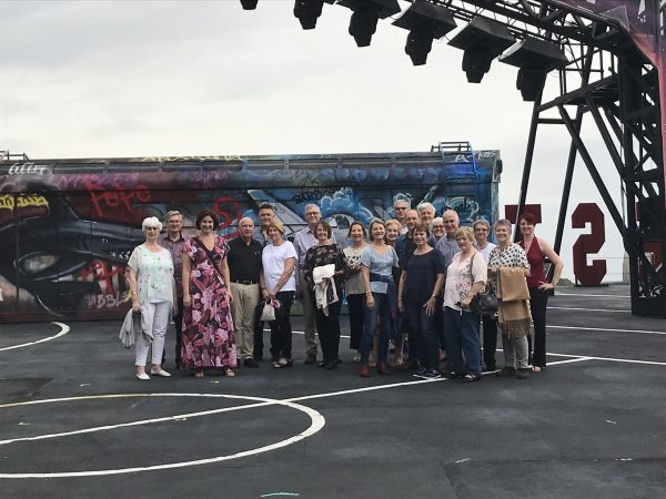 A diverse group of 21 people surrounded by scenery and props on a backstage tour.