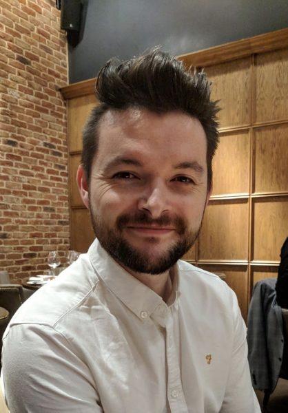 Man wearing white shirt facing camera