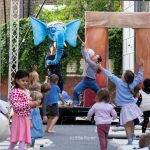 A group of excited children surround a bright blue elephant puppet