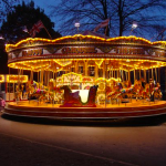 A brightly lit carousel at night with trees in the background