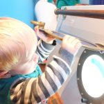 A toddler stands and lifts up a porthole window