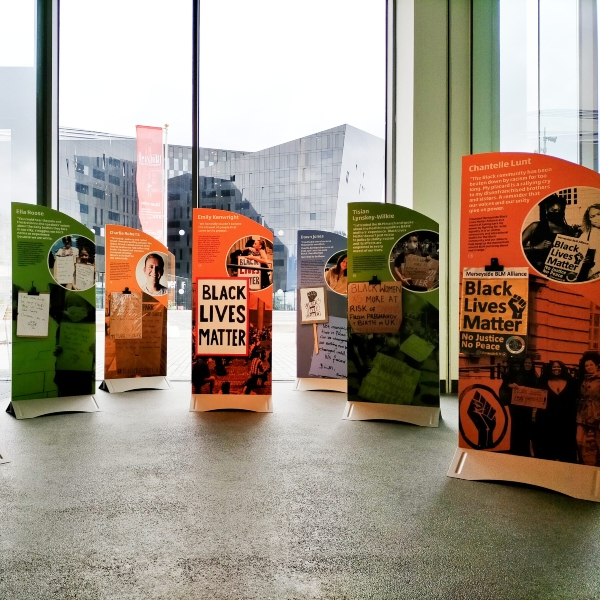6 freestanding displays in orange and green with photographs and text saying Black Lives Matter