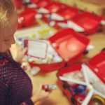 A small girl plays with lots of fun objects from an array of red cases