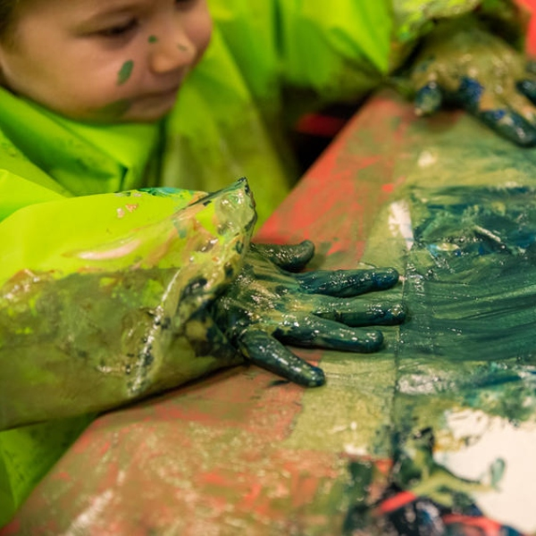 A young child covered in green paint uses her hands to make a picture