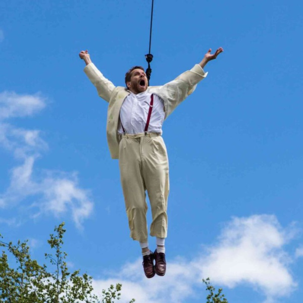 A man in a white suit suspended high in the air above the tree tops by a harness. His arms are out wide.