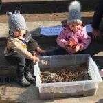 Two warmly dressed toddlers wearing bobble hats play in a large container of sand. They are sat on the steps of a museum