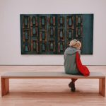 A woman sits alone on a wooden bench staring at a large painting