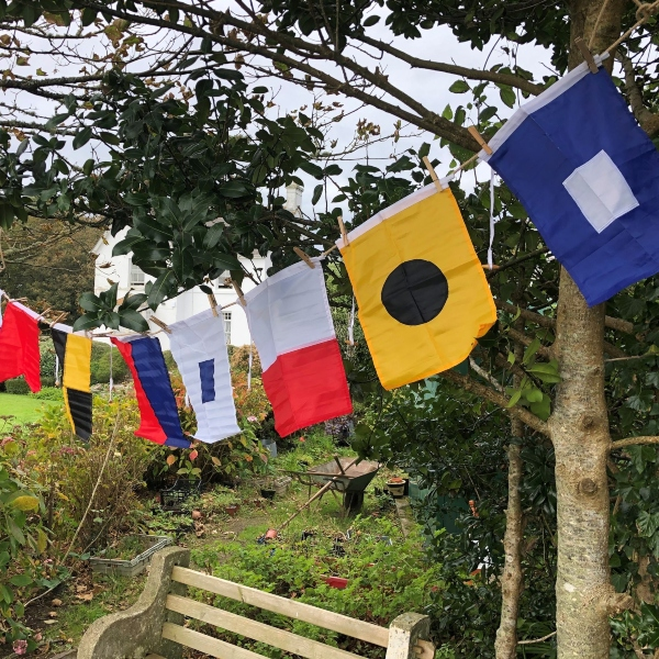 Semaphore flags hanging from a string above a garden bench.