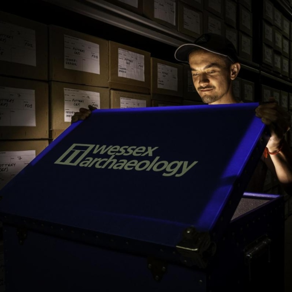 A man opens a large case in a darkened store room