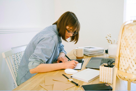 A woman sits at her task making notes.